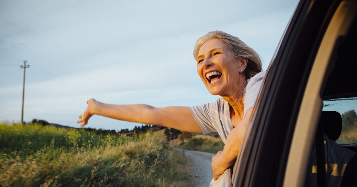 Woman hanging out of car window smiling