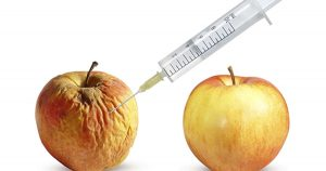 Apple being injected with needle