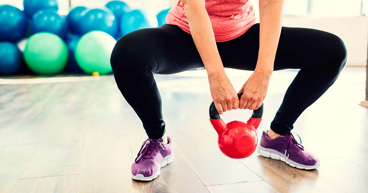 Woman squatting with kettle bell