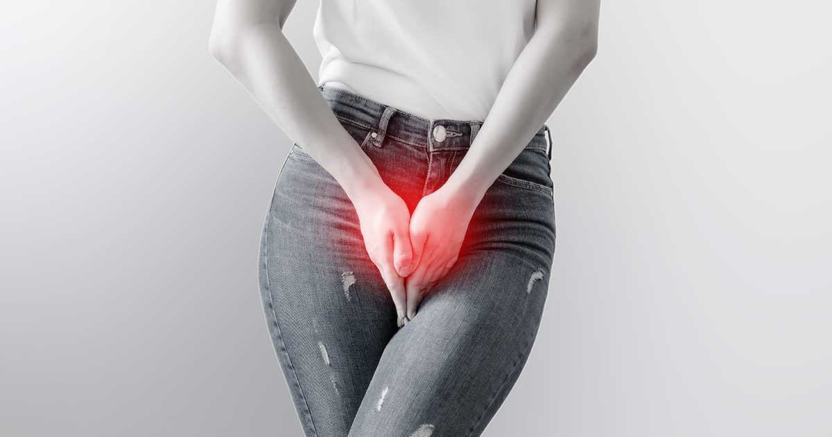 a woman crossing her legs and suffering from the urge to urinate, which is a symptom of both overactive bladder and a UTI